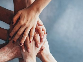 group of hands, one on top of the other from all sides